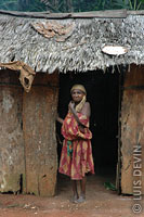 Elderly Pygmy woman in the doorway of a bark hut