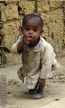 Pygmy child near a mud hut