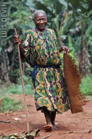 Old Pygmy woman with a mat and a walking stick