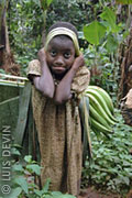 Pygmy girl with a bunch of African green bananas plantains