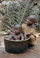 Pygmy baby taking a bath in a pot